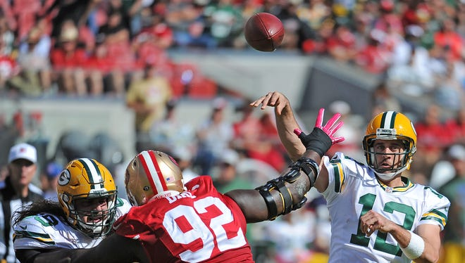 Green Bay Packers quarterback Aaron Rodgers (12) throws under pressure from defensive lineman Quinton Dial (92) as David Bakhtiari (69) blocks against the San Francisco 49ers at at Levi's Stadium in Santa Clara, CA October 4, 2015.