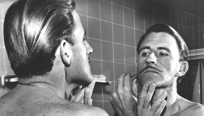 Graham Hill trims his meticulous mustache in 1966.