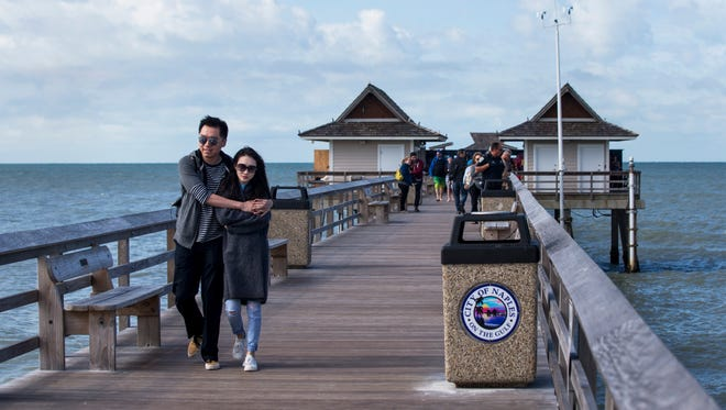 A young couple huddles together to stay warm while walking along the Naples Pier on Tuesday, Jan. 2, 2018. The strong north wind caused temperatures to drop into the low 60s.