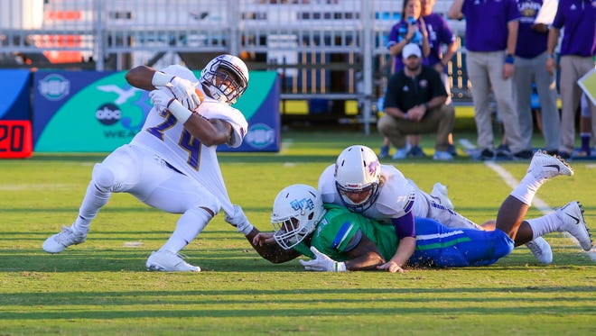 West Florida's Johnathan Coleman (41) busts through the North Alabama offensive line and tackles Damon Cox (24) for a loss at Blue Wahoos Stadium on Saturday, November 4, 2017.