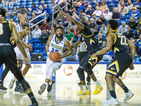 Delaware's Cazmon Hayes drives and eyes the basket in Blue Hens' loss to Towson Saturday.