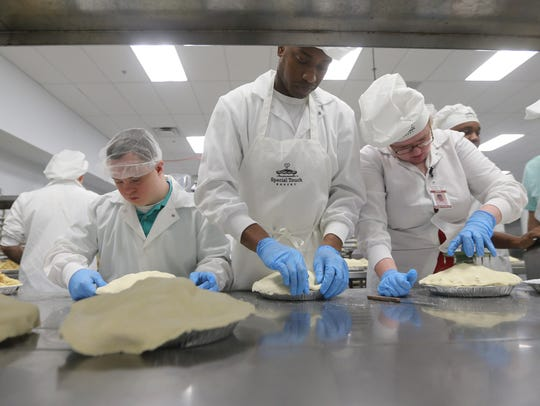 From left, Andrew Sleeman, Akil Anderson and Megan Seedhouse make apple pies at Special Touch Bakery.