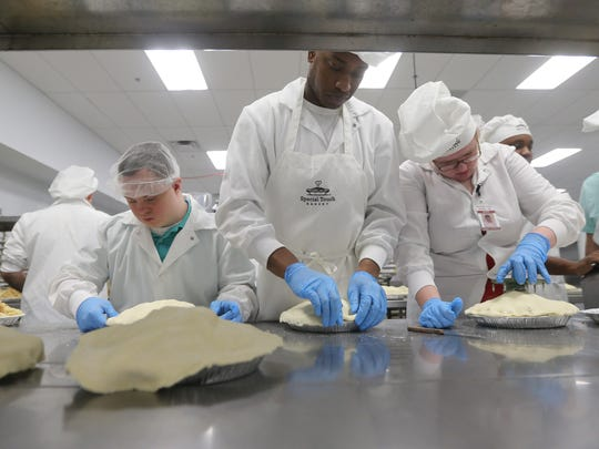 Andrew Sleeman (L-R) Akil Anderson and Megan Seedhouse make apple pies at Special Touch Bakery.