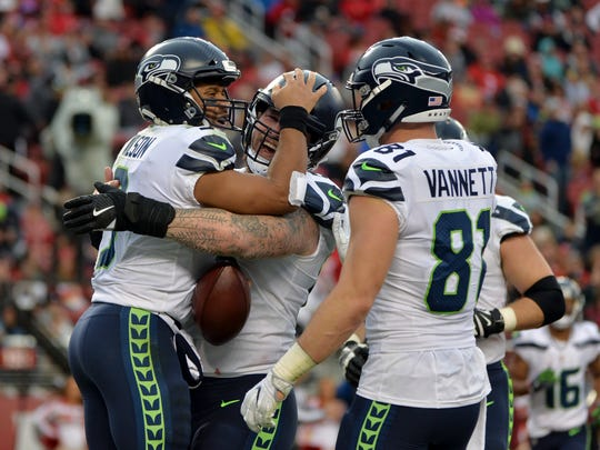 Seattle Seahawks quarterback Russell Wilson, left, is hugged by teammates after scoring on a rushing touchdown against the San Francisco 49ers during the first half of an NFL football game Sunday, Nov. 26, 2017, in Santa Clara, Calif. (AP Photo/Don Feria)