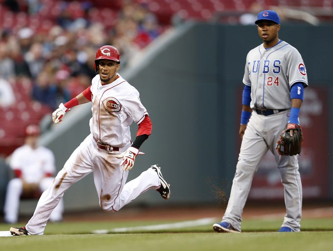 Cincinnati Reds center fielder Billy Hamilton (6) lands on third base after a wild pitch to  first baseman Joey Votto (19) against the Chicago Cubs.