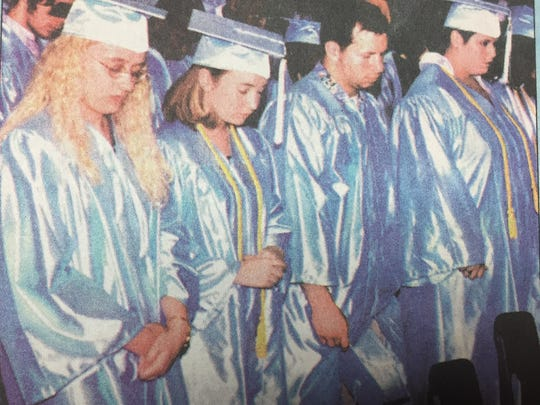 From left, Dawn Vincent, Stephanie Utley, Josh Turner, and Nicole Trainer bow their heads for the graduation benediction in June 2001.