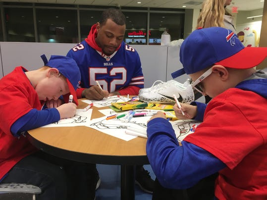 "Buffalo Bills linebacker Preston Brown, center, is joined by Will Lucas, left, and Ian Cameron, right, in helping design customized cleats at Buffalo's John R. Oishei Children's Hospital on Tuesday, Nov. 14, 2017. Brown will be one of three players to wear the customized cleats during Buffalo's home game against the New England Patriots on Dec. 3. The event was held as part of the NFL's ""My Cause, My Cleats"" campaign in which players are allowed to wear their own style of footwear reflecting their commitment to charitable causes. (Photo by John Wawrow)"