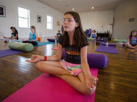 Michelle Kass, 11, meditates at Kids Yoga Camp.