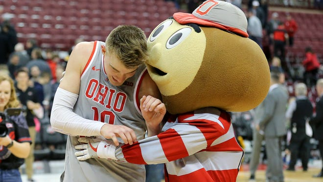 Ohio State Buckeyes forward Justin Ahrens celebrates with mascot Brutus Buckeye after leading the team in scoring against the Iowa Hawkeyes at Value City Arena in Columbus, Ohio.