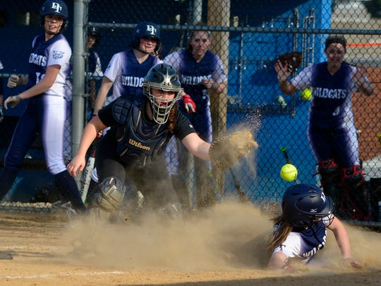 Dallastown's Krista Flemmens slides into home safely as Kennard Dale catcher Katelyn Mayle loses the ball, Thursday March 24, 2016. John A. Pavoncello photo