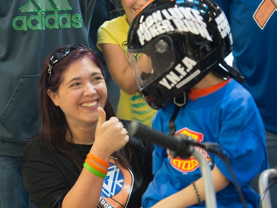 """Stacy Steigelman gives her son, Lucas, a thumbs up after the 2nd Amendment Lebanon County chapter of the Iron Order Motorcycle Club presented a minibike to Lucas  on Thursday, Sept. 22, 2016, at Iron Valley Harley-Davidson. Lucas was diagnosed with leukemia in January. The Y.N.F.A stands for """"You'll Never Fight Alone."""""""