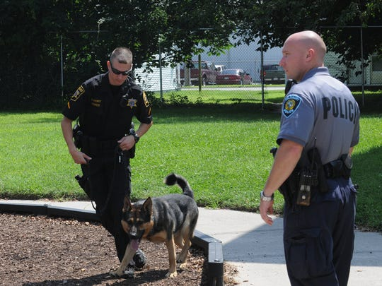 Wicomico County Sheriff Department Deputy First Class M. Jones and his dog, Fiasko, and Salisbury Police Cpl Jason King search the playground of Pemberton Apartments Tuesday in connection with a 2007 shooting.