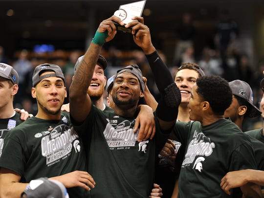 Michigan State's Branden Dawson lifts the Most Outstanding Player trophy after beating Michigan to win the Big Ten Basketball Tournament inside Bankers Life Fieldhouse, March 16, 2014.
