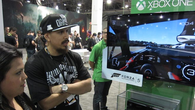 Janet Avila, 25, and fiancé David Ureno, 25, both of Hollister, Calif., check out Forza Motorsport 5 on the Xbox One video game system at GameStop's Expo in Las Vegas.