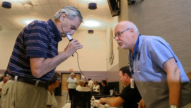 John Hill (right) director of Respiratory Care Services at Deborah Heart and Lung Center gives a lung test to Arlington Work of Toms River, N.J., at Toms River High School East on Friday Aug. 23, 2013.