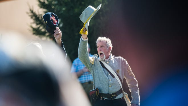 Re-enactor Eddy Sandstrom from the Daniel Lady Farm cheers on the riders of the Pennsylvania Patriot Guard during a ceremony in Gettysburg on Friday Aug. 19, 2016 as the riders transport the remains of a Civil War veteran to his home state of Maine.
