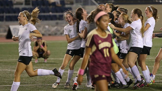 The Penn Kingsmen celebrate winning the Indiana class 2A girls soccer state championship in the background as Brebeuf Jesuit Braves Leigh Ann Roth (11) leaves the field in the foreground, at IUPUI's Carroll Stadium, Indianapolis, Saturday, October 29, 2016. Penn High School won, 2-0.