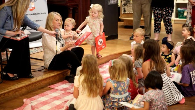 """Toni Tyler's granddaughter, Olive, 17 months, sits in her lap as she reads from her debut children's book, """"Annie Em's Red Shoes"""" at Parnassus Books in Nashville. Granddaughter Abby, 2½, looks on."""