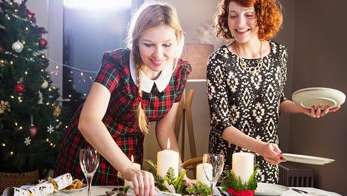 Women preparing Christmas dinner table.