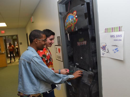 """Senior Tarus Tolbert (front, left) and junior Benjamin Kaplan (back, right), both Student Council members at Pineville High School, """"play"""" a decoration on the classroom door belonging to civics teacher Stacey Sims. It was made to look like an Arcade game from the 1980s. Pineville High School held a parents' night with a """"Back to the Future""""/1980s theme Tuesday. The purpose of the night was to welcome parents and show them how to support their children."""