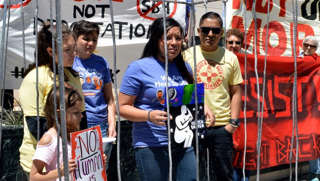 In this May 1, 2017 file photo, immigrant rights advocates speak out against immigration policies of President Donald Trump while placing themselves in mock detention in Albuquerque, N.M., to mark May Day.