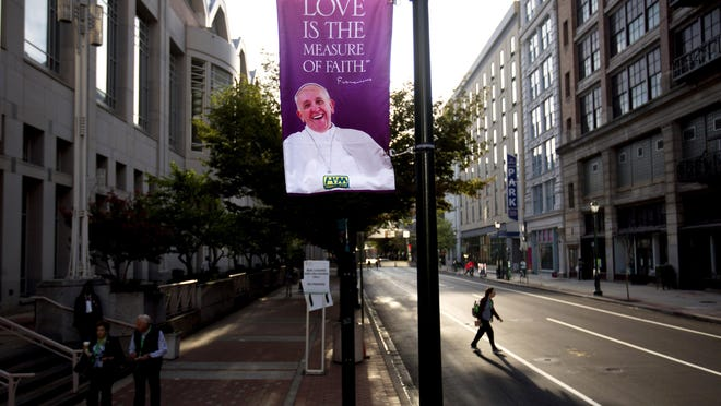A banner bearing the image of Pope Francis hangs outside the Pennsylvania Convention Center ahead of Francis' visit to Philadelphia, Friday, Sept. 25, 2015. Francis wraps up his U.S. visit this weekend in Philadelphia, where he speaks in front of Independence Hall and celebrates Mass on the Benjamin Franklin Parkway to close out a big rally on Catholic families. (AP Photo/David Goldman)