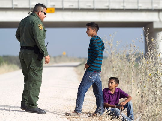 Two young unaccompanied Honduran boys turn themselves into a Border Patrol agent near the Anzalduas International Bridge not far from the Rio Grande river in Mission, Tex., on Saturday, June 21, 2014. Alone the boys walked down a dirt road coming from the Rio Grande, sat down at the end of the road and waited till they turned themselves into the agent.