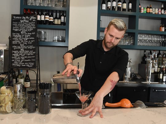 Bartender Tyson Bierwolf crafts a cocktail at Reno Provisions. The bar runs along one side of the seat-yourself café that looks onto North Sierra Street.