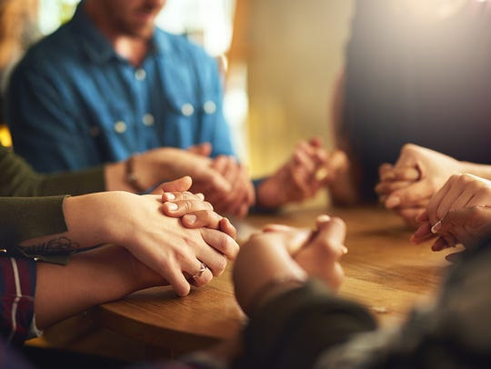 Shot of a group of people holding hands and praying