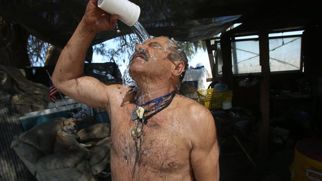 """""""God will take care of me,"""" said Joaquin Escobar in Spanish as he pours water over his head to cool off during this region's excessive heat warning. One of two men living in an abandoned boat in Coachella, he accepted supplies offered Saturday by workers from the Coachella Vallery Rescue Mission in Indio."""