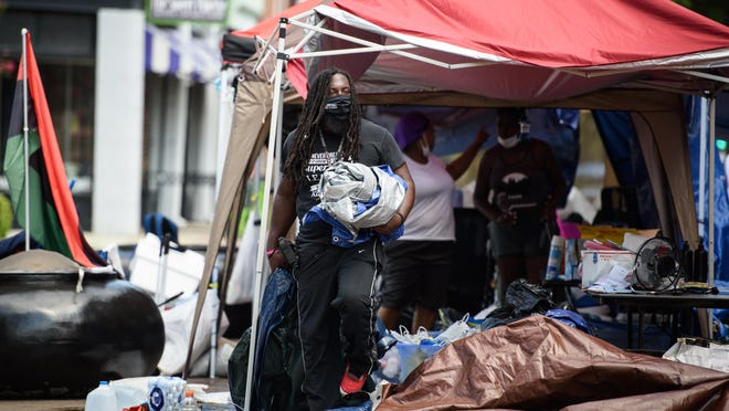 Members of The Ville's Voice take down the encampment at the Market House. Representatives of the group said they could return in 60 days if their demands on police reforms and other issues are not met. They also said they will return to the Market House a few times a week to help feed the homeless.