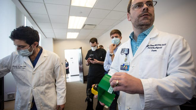In this April 28 photo, Alexander Faigen, left, and Jeffrey James, right, both of Augusta University's Dental College, discuss the 3D printing process for nasal swabs.