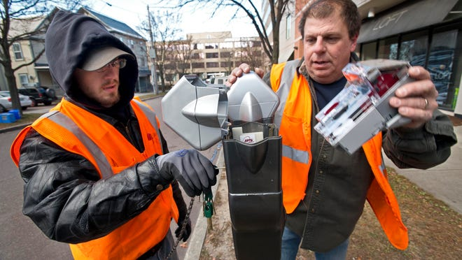 Dylan Boardman, left, and Dan Hill from Burlington's Department of Public Works install new parking meters downtown Wednesday.