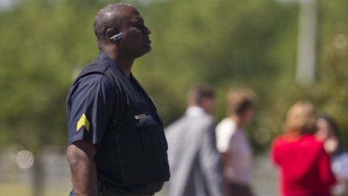 A police officer stands guard at a UPS warehouse on Tuesday, Sept. 23, 2014, in Birmingham, Ala. A UPS employee opened fire Tuesday morning inside one of the company's warehouses in Alabama, killing two people before taking his own life, police said.