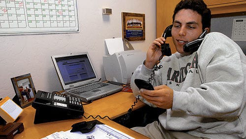"Memphis coach Josh Pastner, shown here at his previous job as an assistant at Arizona, still uses a flip phone or as he calls it, a ""dinosaur phone."""