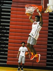 Mekhi Lairy dunks the basketball while teammate Jaylin Chinn waits for his shot at the rim.