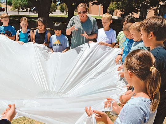 Judith Ortego from the Carlsbad Soil and Water Conservation District teaches fourth grade students from Riverside Elementary School about a watershed using a tarp for illustration. The students had to hold onto the tarp and work together to keep the water in the middle from falling to the ground.