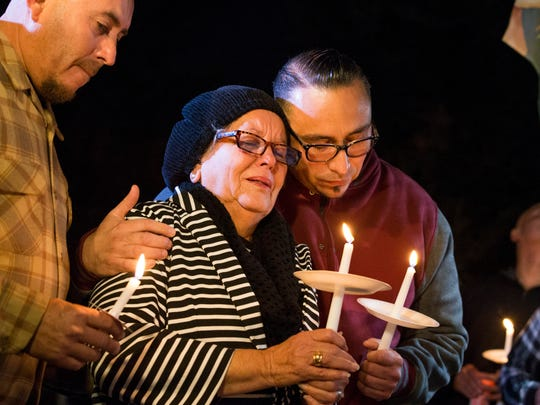 In this photo provided by The Bakersfield Californian, Rubia Serna is consoled by her sons Jesse Serna, right, and Frank Serna at the candlelight vigil for Francisco Serna, 73, her husband and their father, Tuesday, Dec. 13, 2016, in Bakersfield, Calif.  Francisco Serna was shot and killed by a Bakersfield, Calif., police officer near his home early Monday morning. Police Chief Lyle Martin said Tuesday that the unarmed Serna refused to take his hand out of his pocket when he was shot by an officer who thought he had a gun. Serna's family said he suffers from dementia and he often took walks in the evening.