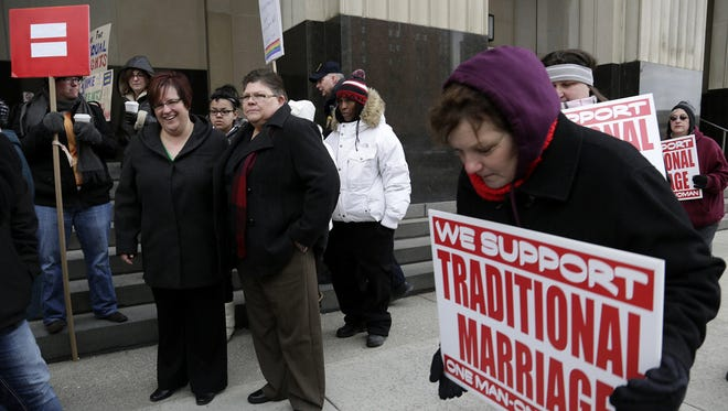 April DeBoer, left, and her partner Jayne Rowse are the plaintiffs in the Michigan case to lift the ban on same-sex marriage in the state. The couple is surrounded by protesters and supporters outside court in Detroit on Tuesday, Feb. 25, 2014.