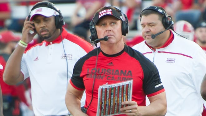 UL coach Mark Hudspeth, flanked here on the sideline by assistants Marquase Lovings (left) and Mitch Rodrigue (right) during a 2016 game against Idaho, is in Nashville this week looking to fill a staff vacancy.