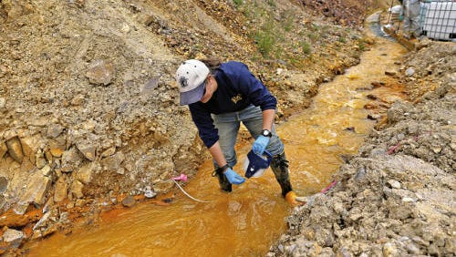 Weston Solution Inc. assistant engineer associate Megan Oller  measures water flow coming out of Gold King Mine north of Silverton, Colo., where more than 3 million gallons of heavy-metal laden mine waste was accidentally released into the Animas River. New Mexico officials were not informed of the spill until nearly 24 hours after it happened, and it wasn't the first time notification of a mine spill in that area was delayed.