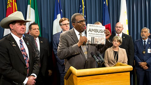 State Sen. Royce West holds up a copy of the Dallas Morning News published the morning after a sniper killed five police officers and wounded several others on July 7, 2016.