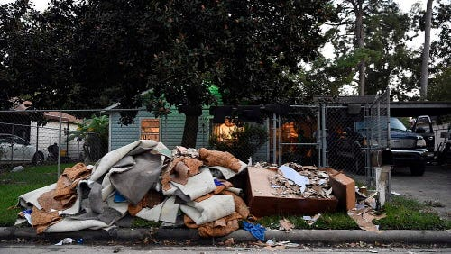 Wet carpet, dry wall, and furniture sit outside of Frances Cirilo's home in East Houston.