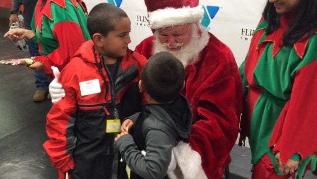Alejandro Cantu, 8 (from left), and his brother Ruben Cantu, 5, chat with Santa Claus during the Shoes for Kids holiday party Friday, Dec. 9, 2016, at the YMCA.