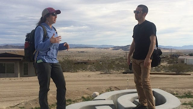 Artist Gregory Michael Hernandez works with Mojave Desert Land Trust environmental site coordinator Lesley Hughes ahead of the Joshua Treenial.