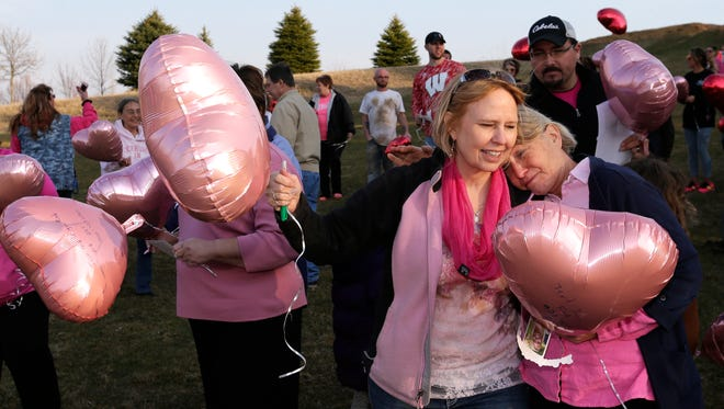 "Bev Kelley-Miller, left, gets a hug from friend Babs Smith of Appleton during a balloon release to celebrate the ""angelversary"" of Bev's daughter, Megan Kelley, Thursday at Memorial Park in Appleton. Kelley-Miller has been on an advocacy mission regarding drug addiction since Megan died of a heroin overdose a  year ago."