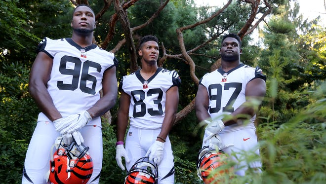 """Cincinnati Bengals Carlos Dunlap, Tyler Boyd and Geno Atkins pose in their white and black-accented """"Color Rush"""" uniforms the Bengals will wear when they play the Miami Dolphins Sept. 29. The debuted the new uniforms at the Cincinnati Zoo and Botanical Garden's white tiger exhibit."""