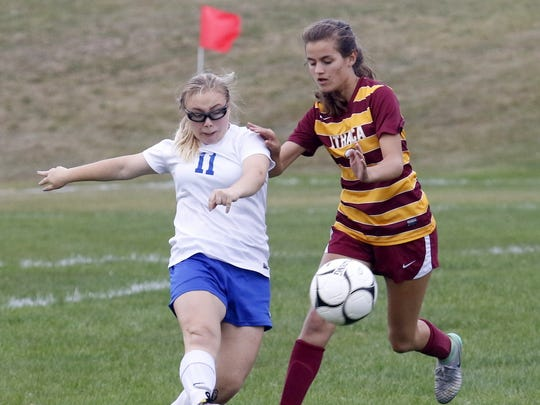 Jade Munson (11) of Horseheads kicks the ball as Ithaca's Erin Dracup closes in Thursday during the Little Red's 3-0 win in Horseheads.
