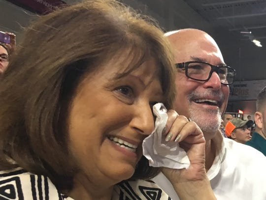 Naples' Debbe Schertzer, with husband Danny Schertzer, dabs away tears watching her daughter, Courtney Faunce, receive her master's degree in counseling during FGCU's commencement in Alico Arena on Saturday, Aug. 5, 2017.