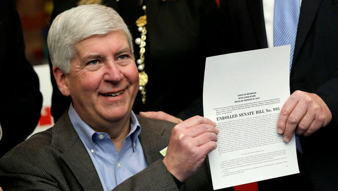 Gov. Rick Snyder poses for a photograph after signing legislation that establishes comprehensive regulations for the testing, use and eventual sale of autonomous vehicle technology at the Automotive Hall of Fame in Dearborn on Friday December 9, 2016.